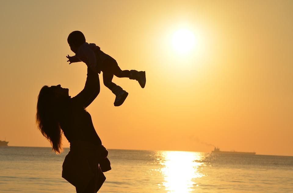 Madre alza a su hijo en un día de playa